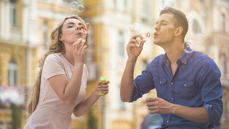 Playful couple blowing soap bubbles, enjoying time together, summer date royalty free stock image