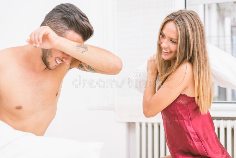 Playful couple playing in bed stock photography