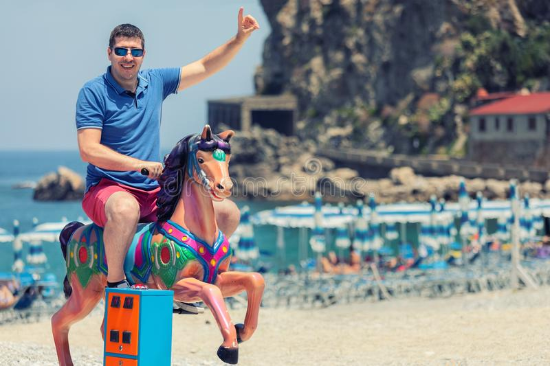 Playful crazy man dad riding wooden rocking horse at beach, Happy adult guy having fun on playground in summer vacation royalty free stock images