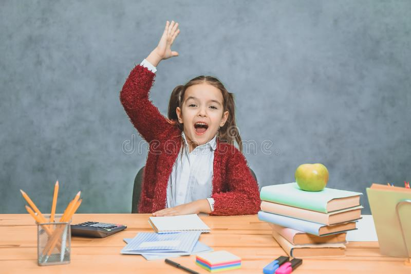 A playful cute little girl is having fun while relying on thick books on a gray background. Her hair is made in stock image