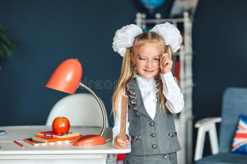 A playful cute little schoolgirl with glasses and a ruler in her hands winks. She having fun while relying on table. Her hair tied royalty free stock photography