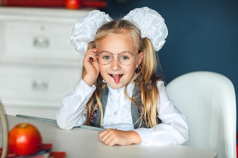 A playful cute little schoolgirl with glasses shows tongue. She sitting at the table, having fun at home. Her hair tied in tails stock photo