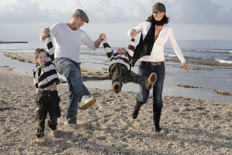 Playful family. Happy family of four playing on the beach stock image
