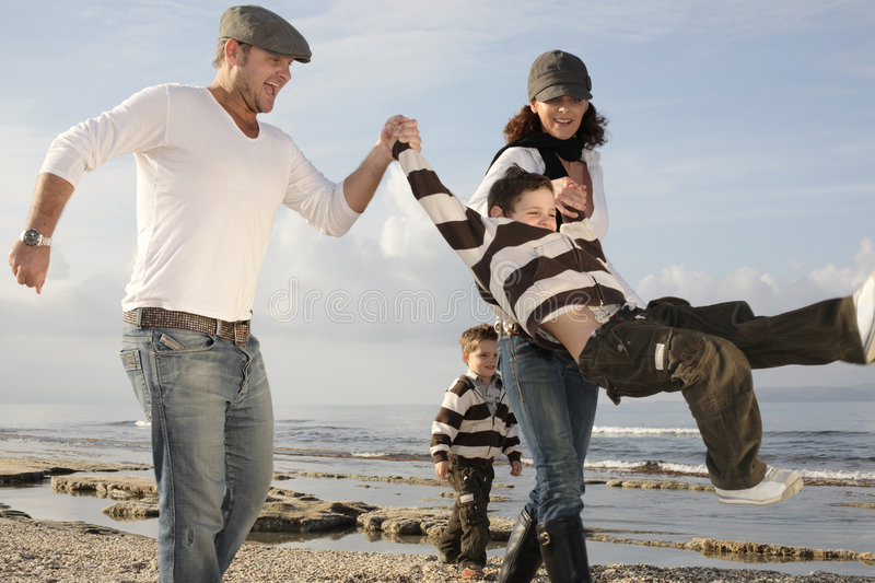 Playful family on the beach. Beautiful family of four on the beach royalty free stock photos