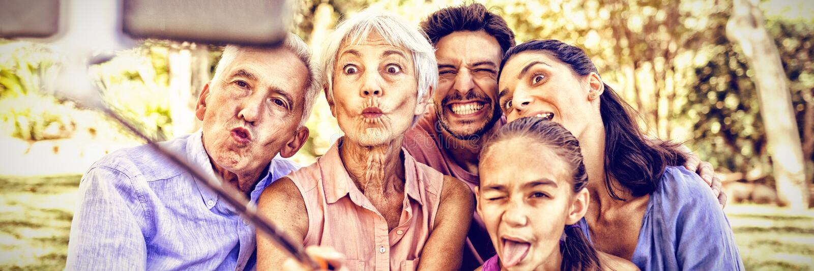 Family making funny faces while taking a selfie in the park stock photo