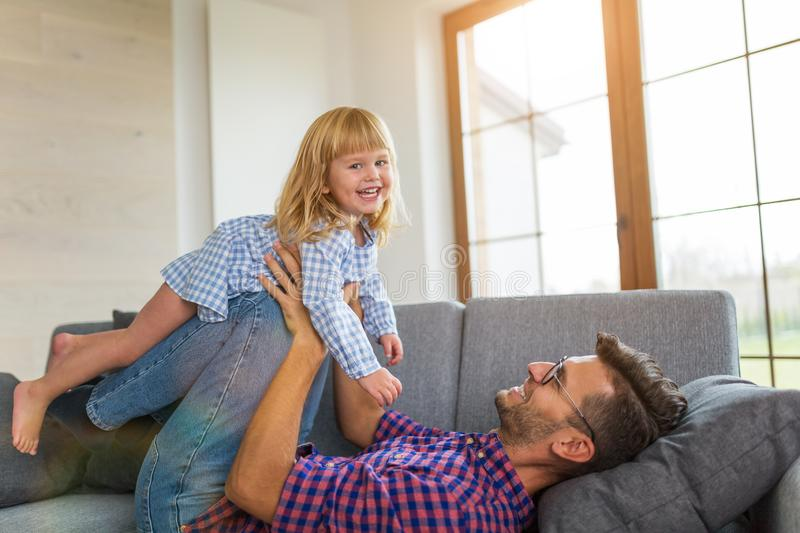 Playful father balancing daughter on legs overhead on sofa stock photography