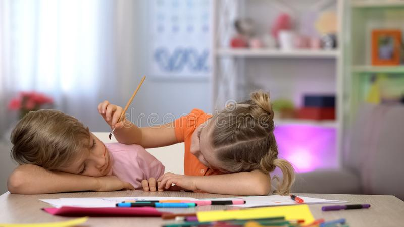 Playful female child painting sleeping brothers face, family joke, fools day royalty free stock photo