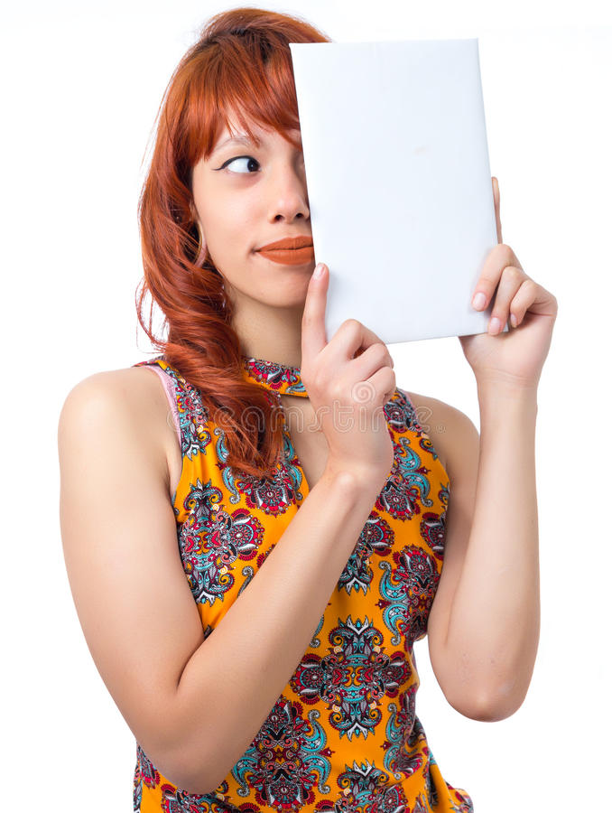 Playful girl covers half of face. Young redhead woman with summer dress.. royalty free stock image