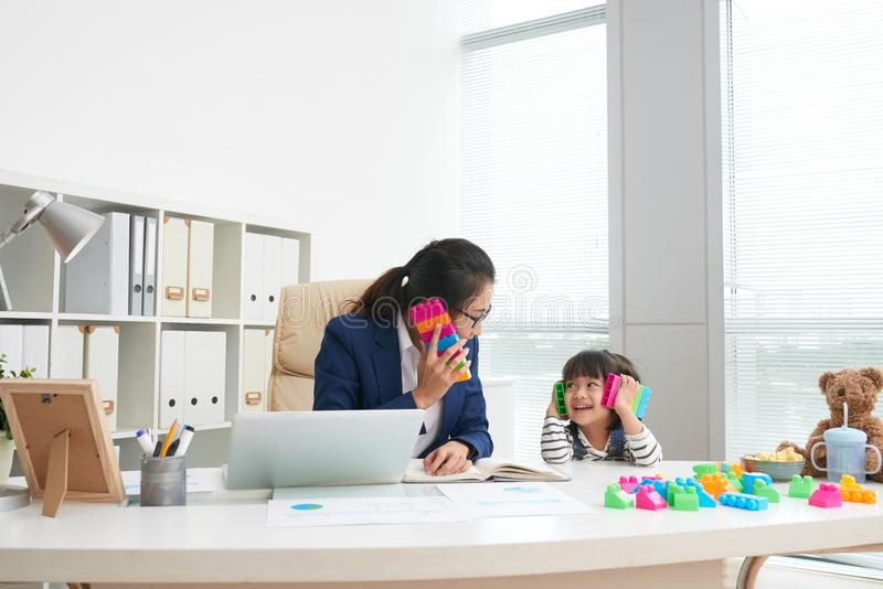 Playful girl with working mother in office royalty free stock photos