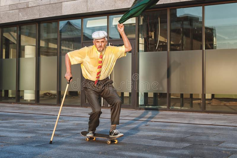 Playful grandfather on a skateboard. royalty free stock images