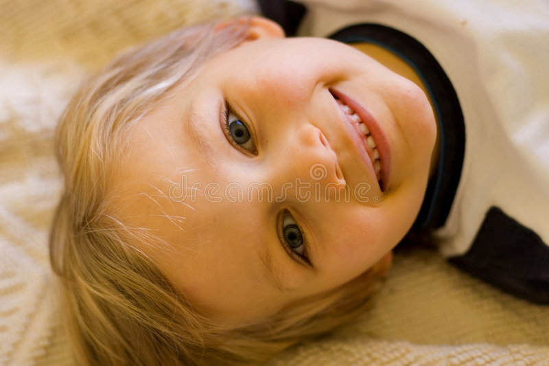 Playful Happy Boy. A young, playful boy with a bright smile poses by lying down for the camera at home royalty free stock image