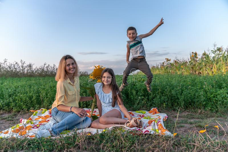 Playful happy family enjoying picnic together , beautiful young mom in yellow shirt sitting on the plaid with her stock photo