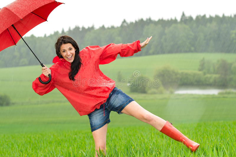 Playful happy girl in the rain. With red umbrella royalty free stock image