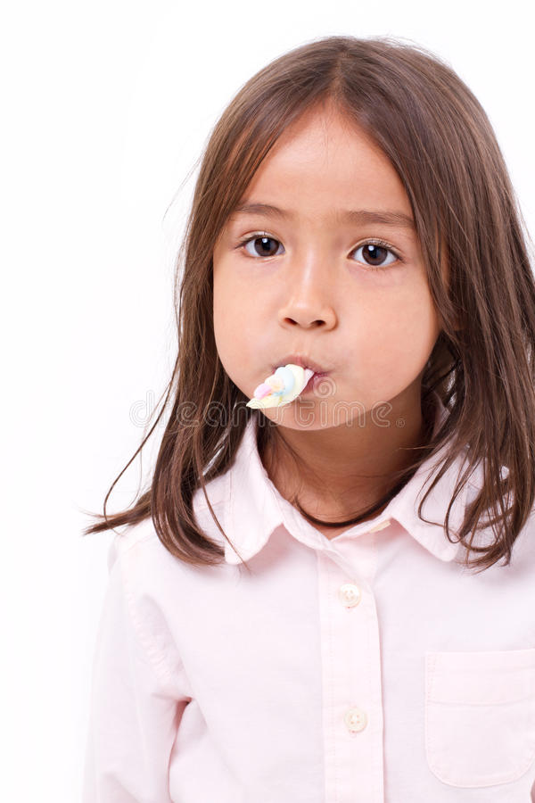 Playful, happy, smiling cute little girl eating marshmallow royalty free stock photos