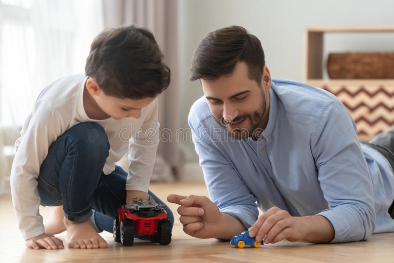 Father and little son racing playing toy cars at home. Playful happy young single father and cute little son racing holding toy cars on warm heated floor at home royalty free stock photos