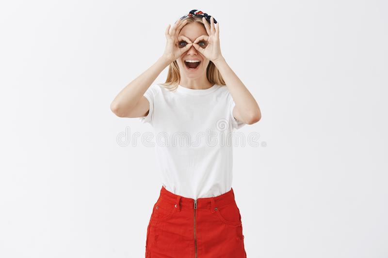 Playful immature good-looking female student with blond hair in red skirt and white shirt showing okay or zero gesture royalty free stock photography