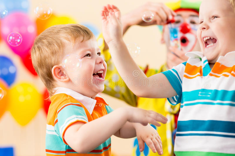 Playful kids boys with clown on birthday party royalty free stock photos