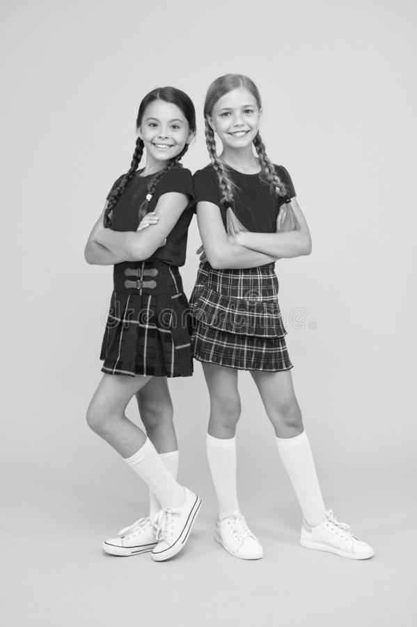 Playful kids. Happy small girls wearing same outfits. Friends enjoying friendship. Happy together. School friends having stock photo