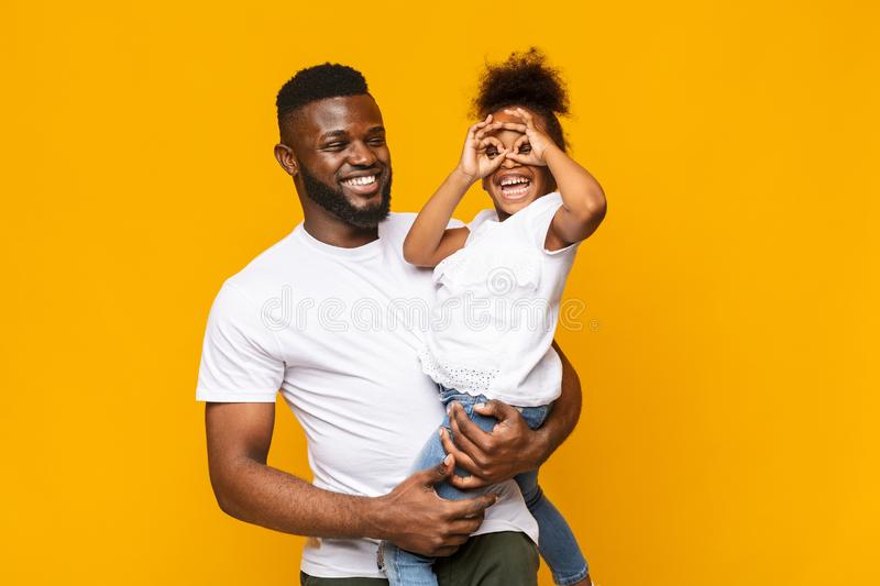 Playful little afro girl making finger glasses, fooling on daddy`s hands. Family fun. Playful little afro girl making finger glasses, fooling on daddy`s hands royalty free stock photography