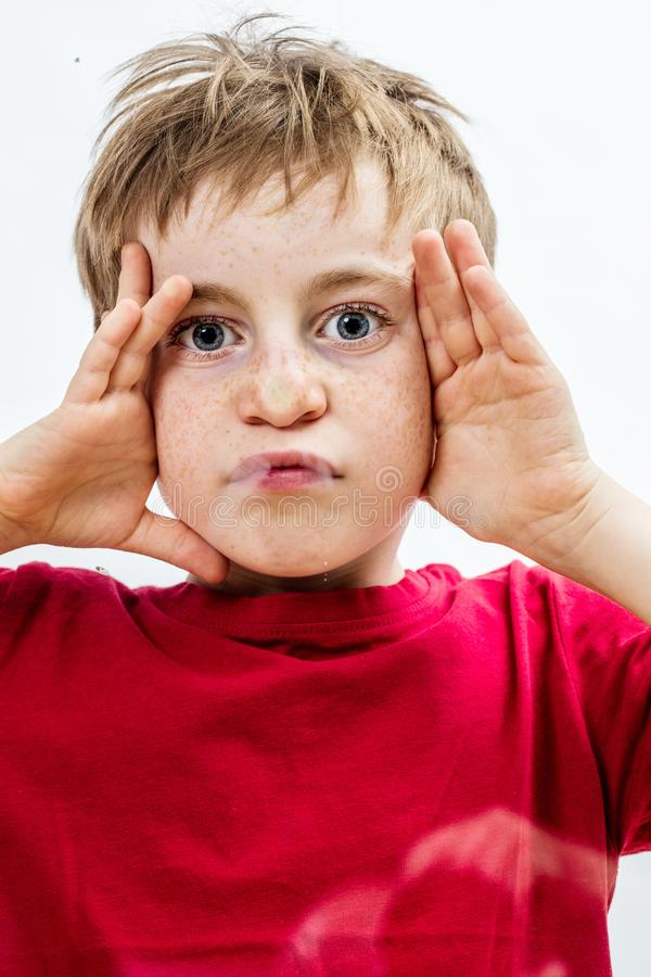 Playful little boy making a crushed grimace, touching his face royalty free stock image