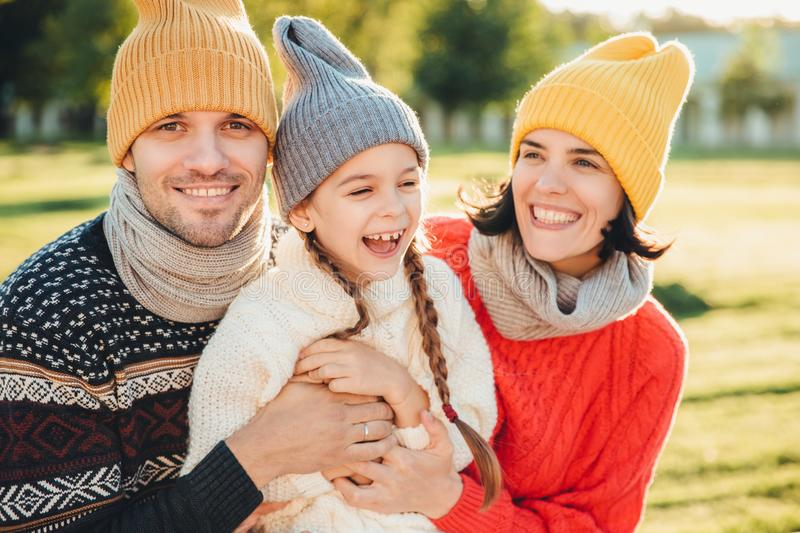 Playful little child with pigtails wears warm clothes, spends free time with lovely affectionate parents, have happy expression, f stock images