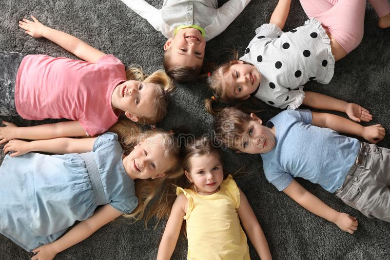 Playful little children lying on carpet indoors royalty free stock images