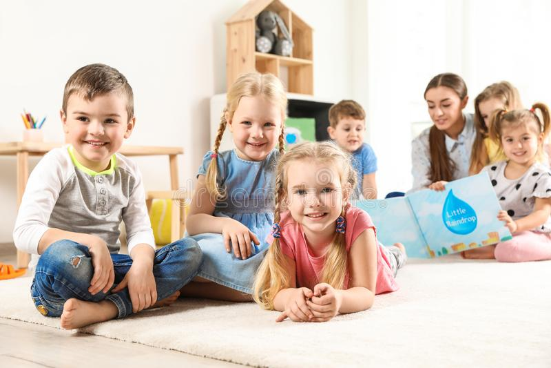 Playful little children resting on floor royalty free stock photo