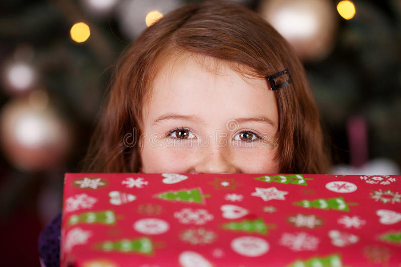 Playful little girl with a Christmas gift. Laughing eyes pf a playful little girl with a Christmas gift peering over the top at the camera royalty free stock image