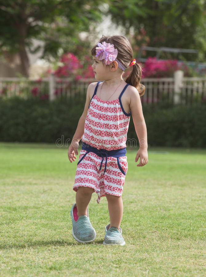 Playful little girl in the park. stock photos