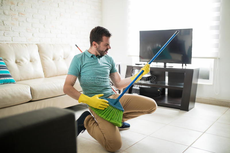 Attractive man using broom as a guitar stock photography