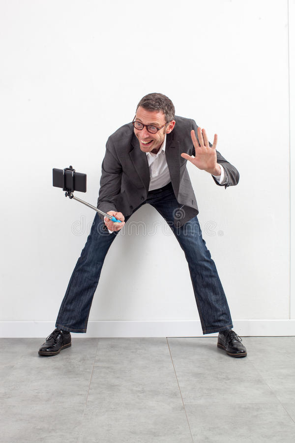 Playful middle aged businessman saying hello on selfie royalty free stock photography