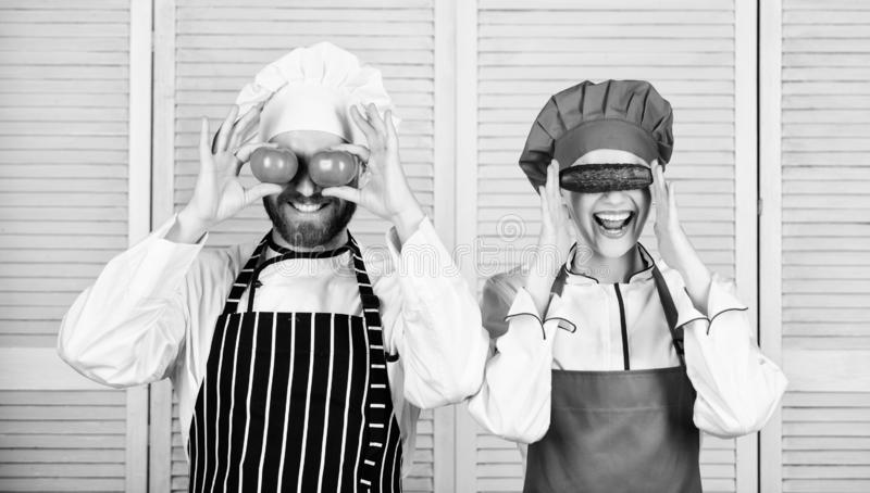 In playful mood. Chef and cook helper playing with vegetables in kitchen. Senior chef and kitchen maid holding tomatoes royalty free stock image