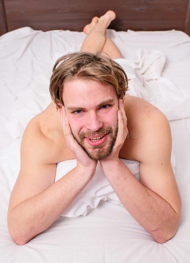 Playful mood concept. Guy macho lay white bedclothes. Pleasant relax concept. Man unshaven handsome happy smiling. Torso relaxing bed. Man feel full of energy stock images