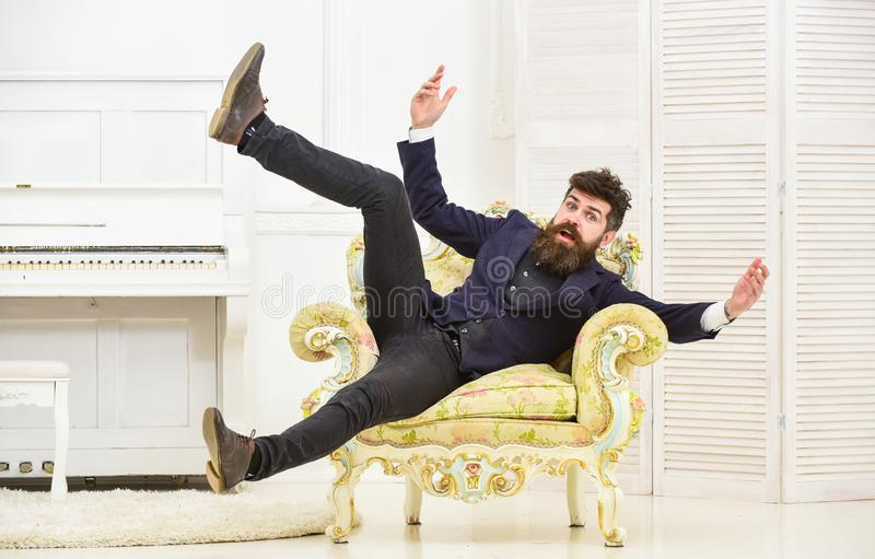 Playful mood concept. Man with beard and mustache wearing fashionable classic suit, sits, jumps on old fashioned stock photo