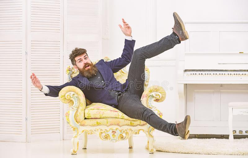 Playful mood concept. Man with beard and mustache wearing fashionable classic suit, sits, jumps on old fashioned. Armchair. Macho attractive and elegant on stock photo