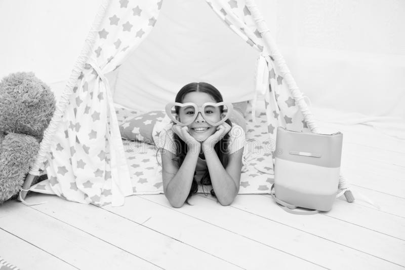 Playful mood. Girl cute child in heart shaped eyeglasses lay relaxing in teepee in her bedroom. Cute space for childrens. Leisure. Modern childrens interior royalty free stock images