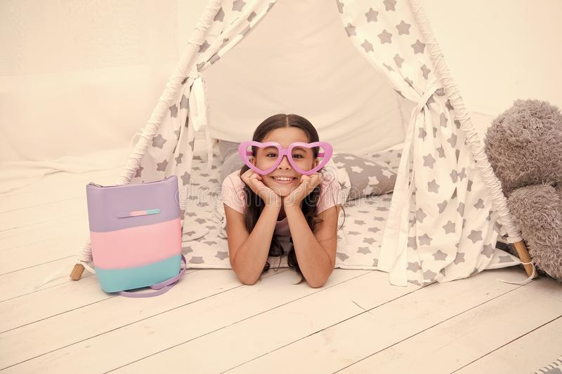 Playful mood. Girl cute child in heart shaped eyeglasses lay relaxing in teepee in her bedroom. Cute space for childrens. Leisure. Modern childrens interior stock image