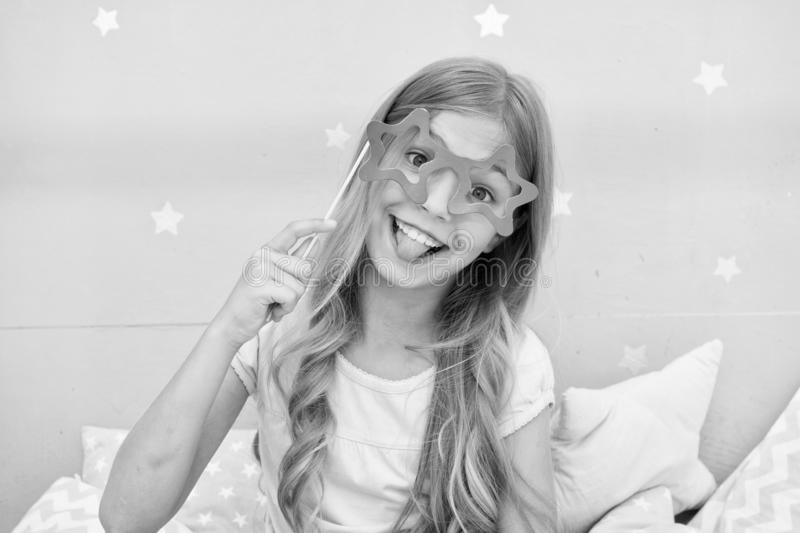 Playful mood. Girl with long blonde curly hair posing with photo booth props. Pajamas party concept. Girl star shaped. Eyeglasses at pajamas party. Cheerful royalty free stock image