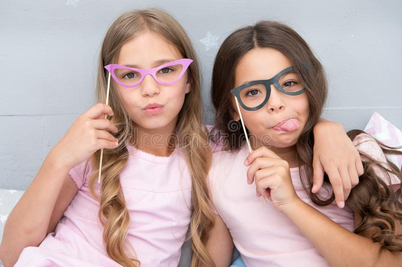 Playful mood. Girls children posing with grimaces photo booth props. Pajamas party concept. Girls friends having fun. Pajamas party. Friends cute and cheerful stock image