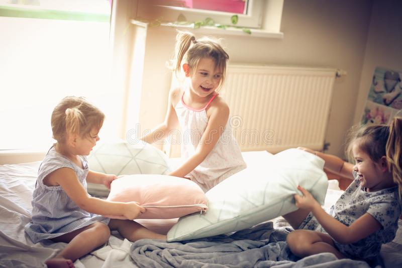 Playful morning in bed. Three little girls playing in bed and having fight with pillow. Space for copy royalty free stock photo