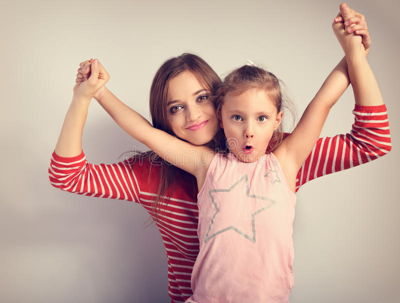 Playful mother and crazy joking grimacing kid holding each other royalty free stock photo