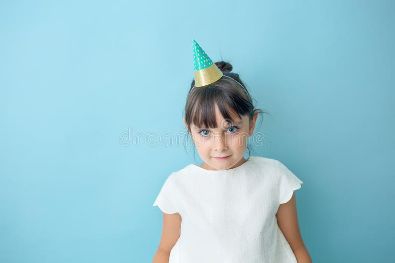 Playful party girl. With a cone hat in front of a blue backdrop stock photos