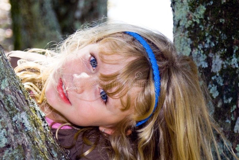 A Playful Pose/young girl. Girl being playful and posing between tree trunks. Her hair is a little wispy, very natural stock photo