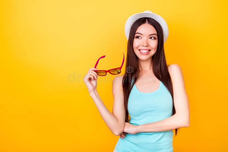 Playful pretty korean female tourist is looking away, wearing summer vacation`s outfit, in hat, holding glasses, stands on yellow stock photos