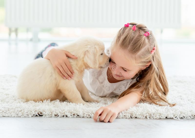 Playful puppy smells happy girl. In light room stock photography