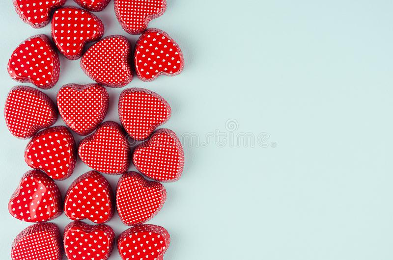 Playful red hearts as border with copy space on fashion mint pastel color background. Modern holiday Valentine`s day backdrop. Playful red hearts as border with stock images