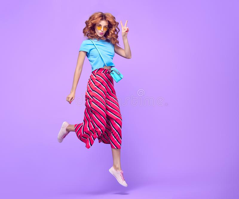 Girl Jumping Having Fun. Fashion Summer Outfit. Playful Redhead Girl with Kiss Face Expression. Beautiful Model Having Fun in Studio on Purple. Young Woman in stock images