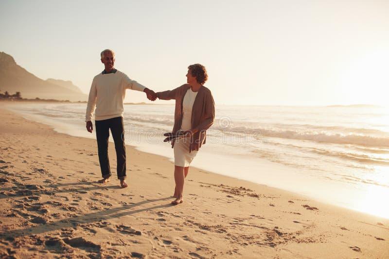 Playful senior couple on the beach stock photos