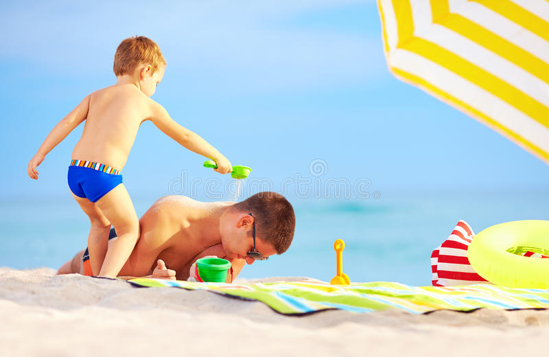 Download Playful Son Strews Sand On Father, Beach Royalty Free Stock Images - Image: 34111929