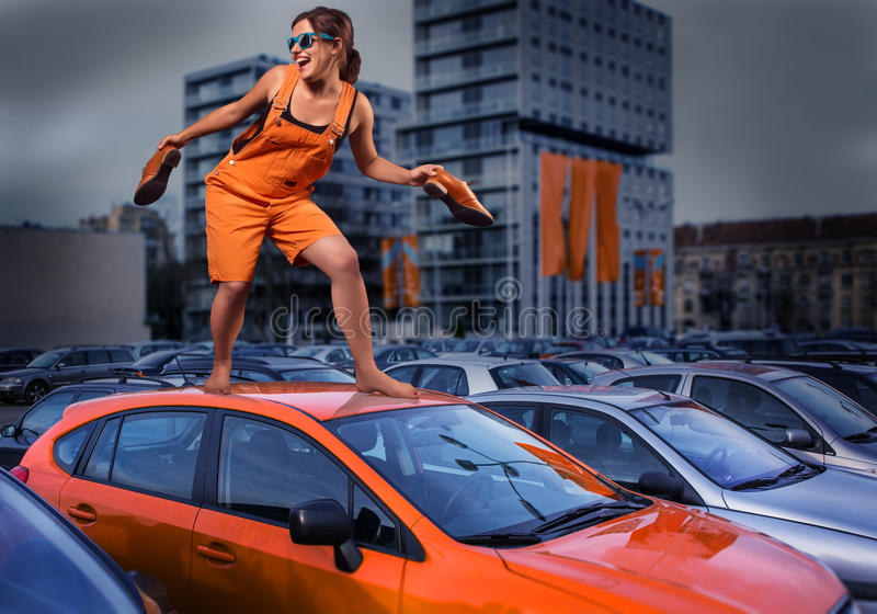 Playful stylish girl in orange overalls standing on car roof in the parking lot stock images